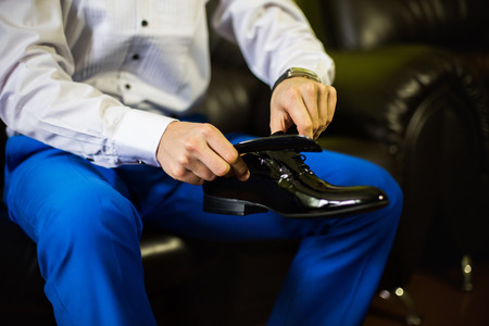 formal dressing: Groom wearing shoes on wedding day, mans style, man legs and hands tying shoe laces, business man dressing up with classic, elegant shoes
