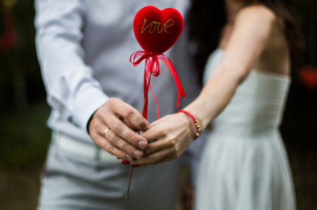 a man and woman holding a heart in his hands, the love between a man and a woman,