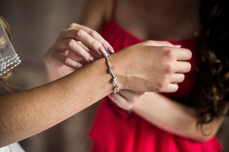 bride bangle: Girl wears a bracelet on a hand of the bride, brides morning, preparing for the wedding, the brides fees, dress, decorate the bride, wedding attributes, jewelery, Stock Photo
