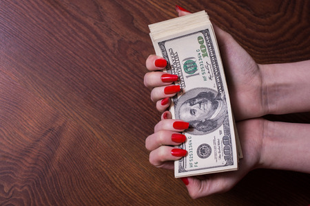 bil: a bundle of money in female hands with red nails, greed for money,  hundred dollar bills front side, old hundred-dollar bil face, copyspace