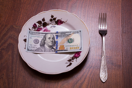 business metaphore: a new  brilliant conceptual idea, picture, hundred-dollar bill lying on a plate, a fork, a bill on the plate on wooden background, hundred dollar bills front side. , new hundred-dollar bil face, the evolution of the bill in one hundred dollars, Breakfast  Stock Photo