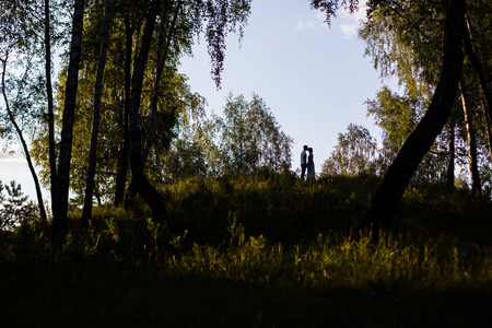 beautiful location: silhouette of kissing couple on a hill, a couple in love in a beautiful location, sunset lighting Stock Photo