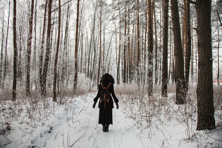 snowscene: girl standing in front of a beautiful winter forest, silhouetted against the winter forest, a man standing on the snow