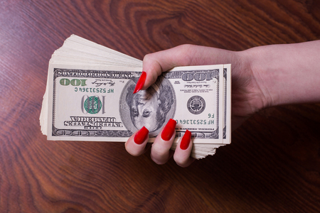 bil: a bundle of money in a female hand with red nails, greed for money,  hundred dollar bills front side, old hundred-dollar bil face