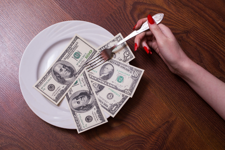 business metaphore: a new  brilliant conceptual idea, photography, one, ten, one hundred dollar bill face, old banknotes lie on a plate, a female hand with red fingernails holding a fork, Breakfast of Champions millionaires, Stock Photo