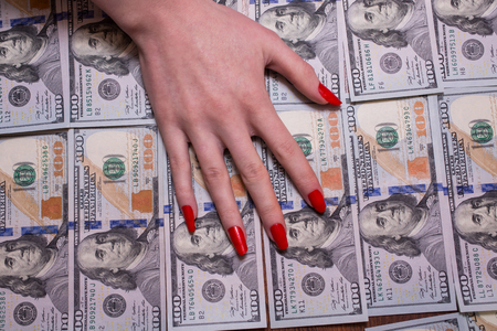 bil: womans hand with red nails lying on the money, greed for money, background of the money, hundred dollar bills front side. background of dollars, new hundred-dollar bil face, the evolution of the bill in one hundred dollars