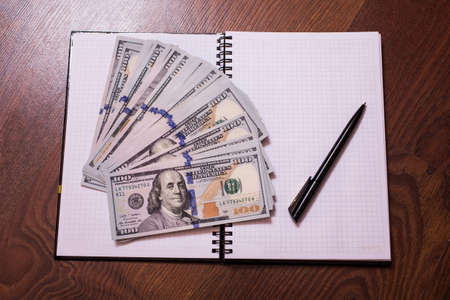 bil: black pen, note book page and money, a place for records, business plan, money background, hundred dollar bills front side. background of dollars, new hundred-dollar bil face, the evolution of the bill in one hundred dollars, copyspace