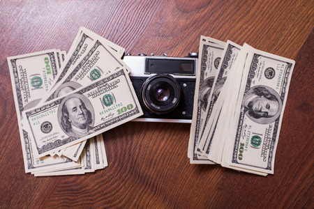 bil: camera and money,business plan, money background, hundred dollar bills front side. background of dollars, new hundred-dollar bil face, copyspace, the work of the photographer, the photographer, earnings in photos Stock Photo