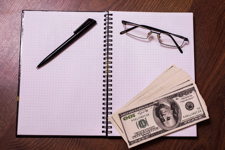 bil: glasses, black pen, note book page and money, a place for records, business plan, money background, hundred dollar bills front side. background of dollars, new hundred-dollar bil face, the evolution of the bill in one hundred dollars, copyspace