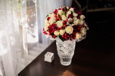 alliances: wedding flowers, bouquet of white roses dairy and red flowers, preparing for the wedding, the grooms fees bride morning Stock Photo