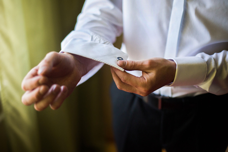 cufflink: man wear a shirt and cufflinks, correct clothes, dressing, mans style, fees groom, wedding preparations, sense of style, correcting sleeves Stock Photo