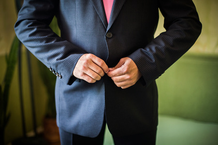 correcting: correct button on jacket, hands close-up, dressing, mans style, correcting sleeves, ready for work, preparing for the wedding