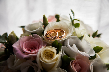 wedding bands: infinity sign of the rings, wedding rings on a white background,wedding bands, wedding rings lie on a bouquet of white and pink, peach roses, a bouquet of roses