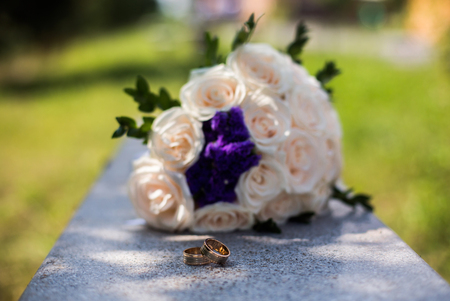 alliances: infinity sign of the rings, wedding rings on a white background,wedding bands, wedding rings lie near bouquet of white and pink, peach roses, a bouquet of roses, wedding flowers