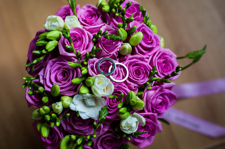 wedding bands: wedding flowers,infinity sign of the rings, wedding rings on a white background,wedding bands, wedding rings lie on a wedding bouquet of beautiful pink roses and white flowers,bouquet of roses, wedding preparation