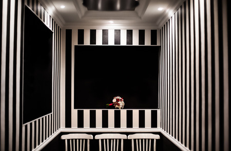 white roses: wedding flowers, white milk, and red roses, bridal bouquet, black and white stripes, zebra, conceptual photography picture, hypnotic background, black chairs, interesting design Stock Photo