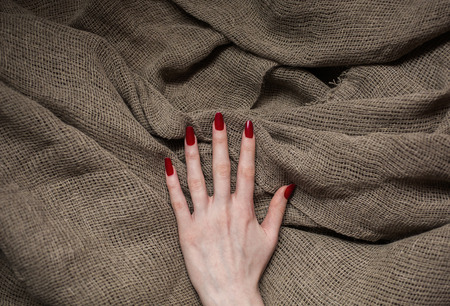 cloth fiber: flax fiber, linen fabric, raw material, cloth bags, linen yarn, female hand with red nails on linen fabric, manicure, feminine long fingers, make clothes Stock Photo