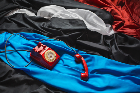 clothes interesting: red dial phone on a crumpled tissue, colored fabrics, raw material, red, black, blue, white cloth, linen cloth, making clothes, an interesting design decision, the game colors, background screensaver