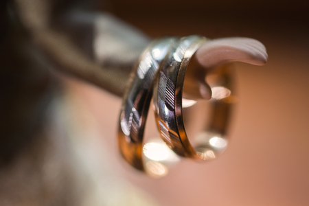 wedding bands: infinity sign of the rings, wedding rings on a yellow background,wedding bands on the hand of doll