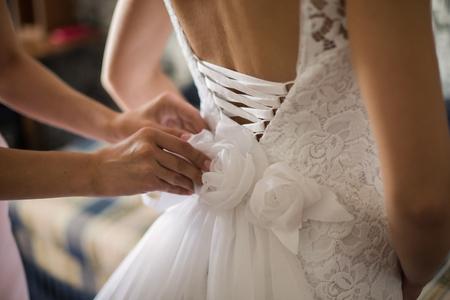신부 웨딩 드레스를 조이다.