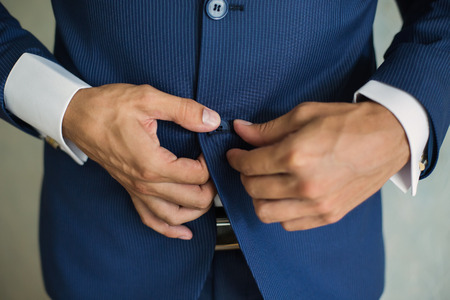 correcting: correct button on jacket, hands close-up, dressing, mans style, correcting sleeves,  preparing for the wedding Stock Photo