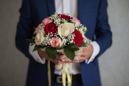 alliances: bride holding a bouquet of white, peach and red roses