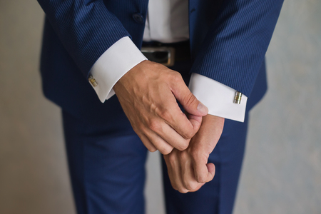 cuff links: man correct sleeves on shirt, hands close-up, dressing, mans style