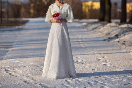 Bride in wedding dress holding a bouquet of red roses, winter wedding Reklamní fotografie
