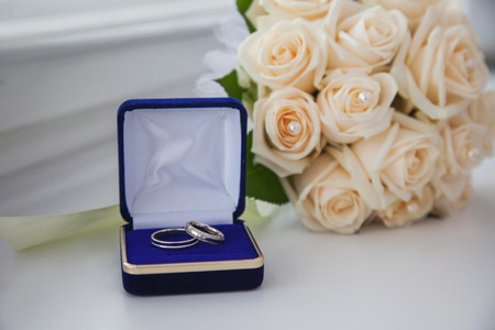 wedding bands: white gold, wedding bands, wedding rings from white gold in the blue box, wedding jewelry, wedding preparation, a bouquet of white roses, white light background Stock Photo