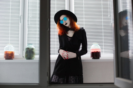 bl: Portrait of red-haired girl in bow tie on a dark background, gothic style girl in black clothes, style fashion, sense of style, girl in dress and in a black cloak, black coat, black lips, a girl standing, round glasses and a hat, in the pot vegetables, bl