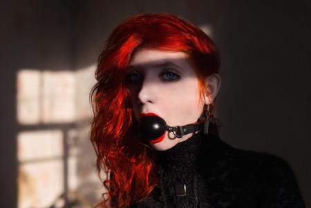 esclavo: chica de pelo rojo con una mordaza en la boca Foto de archivo