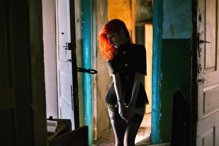 delincuencia: chica de pelo rojo con las manos esposadas