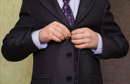 correcting: correct button on jacket, hands close-up, dressing, mans style, correcting sleeves,  boy preparing for the school