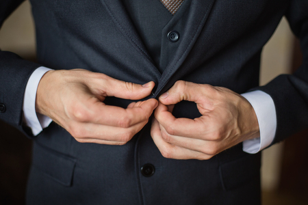 correct button on jacket, hands close-up, dressing, mans style, correcting sleeves,  preparing for the wedding Stock Photo