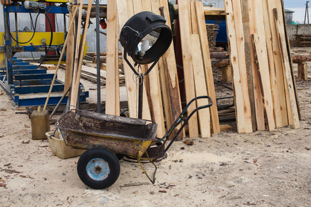 timber harvesting: sawmill, wood processing, timber drying, timber harvesting, drying boards, baulk, a wheelbarrow, a lamp for drying wood Stock Photo