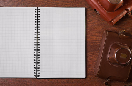 case sheet: a sheet of paper from a notebook, case for the camera on wooden background, copyspace