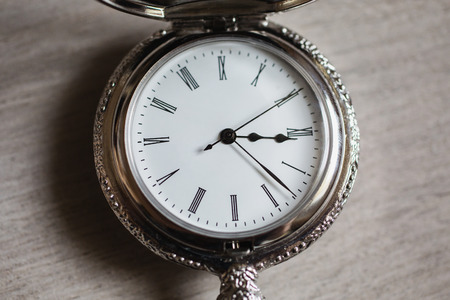 ancient pass: open pocket watch and chain lie on a light wooden table background