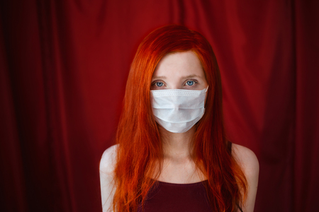 tensed: red-haired girl with a medical mask on a red background, woman doctor, woman with intense look, European, flowing hair