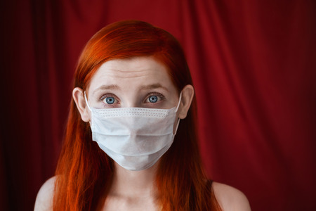 tensed: red-haired girl with a medical mask on a red background, woman doctor, woman with intense look, European appearance, facial wrinkles on the forehead, eared girl Stock Photo