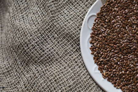 organic flax seed: Flax seeds in a plate on a linen cloth