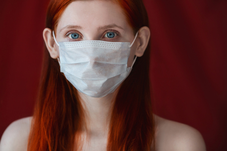 tensed: red-haired girl with a medical mask on a red background, woman doctor, woman with intense look, European, flowing hair, eared girl Stock Photo