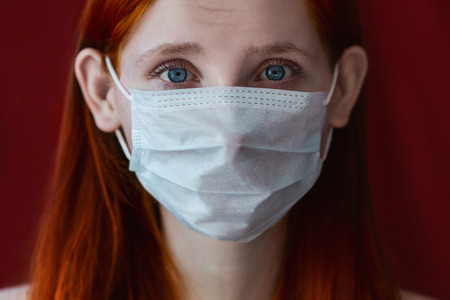 eye red: red-haired girl with a medical mask on a red background, woman doctor, woman with intense look, European, eared girl