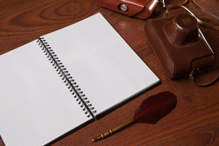case sheet: a sheet of paper from a notebook, fountain pen and case for the camera on wooden background, copyspace Stock Photo