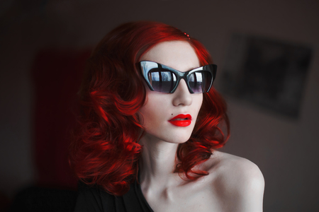 red-haired girl with red lips and pale skin with dark glasses on a dark background, reflection, glasses, stylish woman, red curly hair, bright make-up