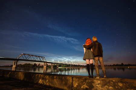 beautiful night scenery, the stars in the night sky, a couple on a background of the night sky, red-haired girl and a guy, noctilucent clouds on the horizon, surface of water, bridge over the river