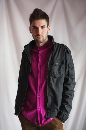 frontal portrait: frontal portrait of a handsome young man with a beard in a purple shirt and a black jacket on a white background with hands in pockets, vertical photo, look at the camera Stock Photo