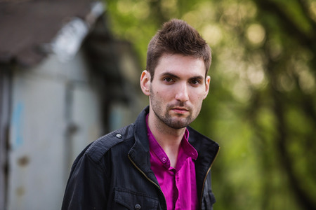 frontal portrait: frontal portrait of a beautiful young brutal man with a beard in a purple shirt and a black jacket on the street look at the camera, street style, on a background of green plants Stock Photo