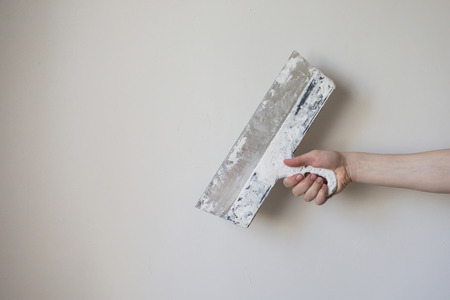 Working tool, spatula in hand on a light background, work plasterer, painter, to make repairs . Trowel in mans hand on a background of a white wall . Space for text