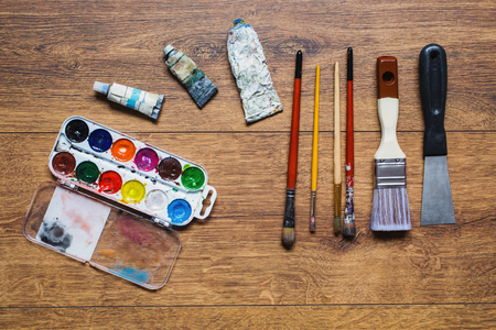 paintbox: Artistic squirrel brushes, tubes of oil paints and watercolors on a wooden background.The palette of twenty-four colors .Used tools for artists and schoolchildren. Tools for art