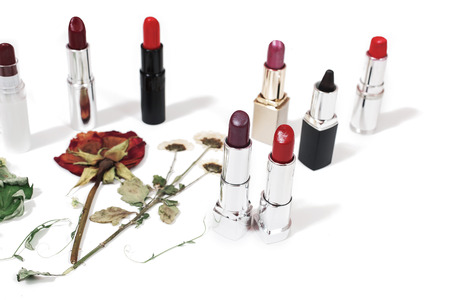 Glossy lipstick on an isolated white background. Lips decorative cosmetics. Dried flowers on a light surface. View from above . Dry rose. Stock Photo